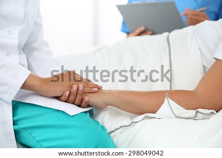 Friendly female doctor's hands holding patient's hand lying in bed for encouragement, empathy, cheering and support while medical examination. Trust and ethics concept. Bad news lessening and support - stock photo