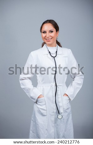 Friendly female doctor with stethoscope isolated over grey background