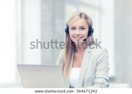 friendly female helpline operator with laptop - stock photo