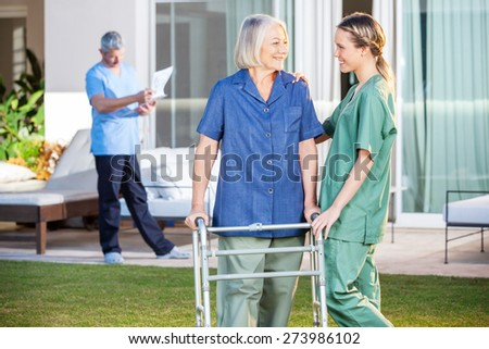 Friendly female nurse assisting senior woman to walk with Zimmer frame in lawn at nursing home - stock photo