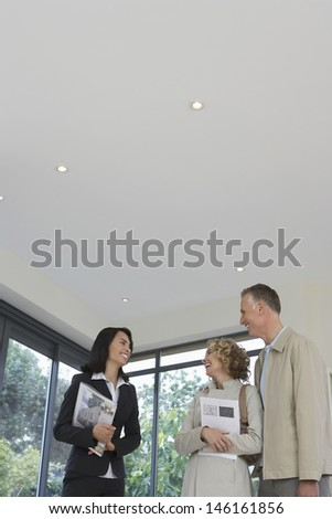 Friendly female real estate agent with happy couple at new property - stock photo