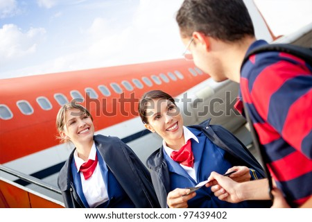 Friendly flight attendants welcoming passenger into the airplane - stock photo