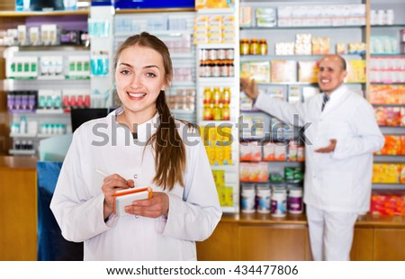 Friendly glad pharmacist and pharmacy technician posing in drugstore