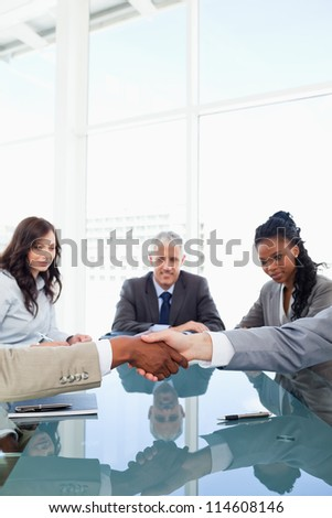 Friendly handshake between two co-workers while their team are looking at them - stock photo