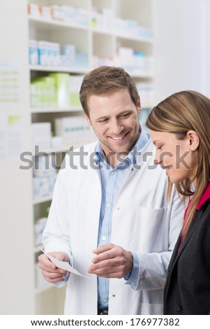 Friendly handsome male pharmacist standing explaining something on a prescription to a woman patient - stock photo
