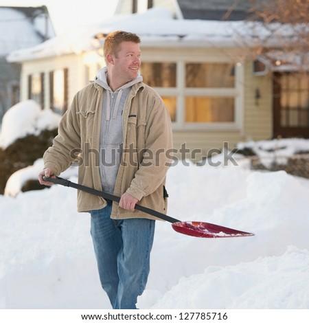 Friendly handsome man shoveling snow - stock photo