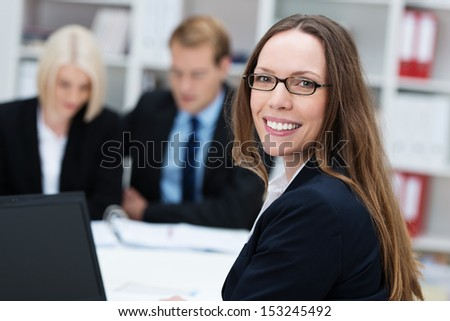 Friendly happy businesswoman wearing glasses with long straight brunette hair turning to smile at the camera while working in an office with her colleagues - stock photo