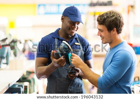 friendly hardware store worker showing customer a sander - stock photo
