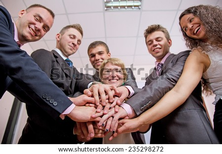 Friendly harmonious business team. Six business people join hands and smiling. Focus is on hands, but face expression is recognizable - stock photo