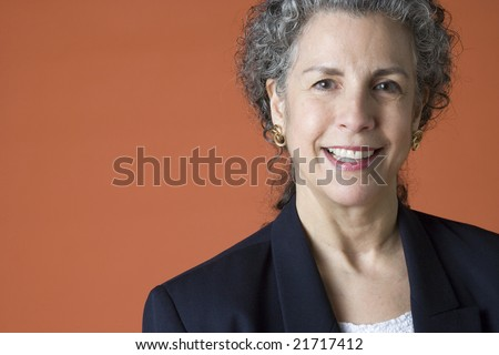 Friendly looking gray haired woman's portrait on a plain background - stock photo