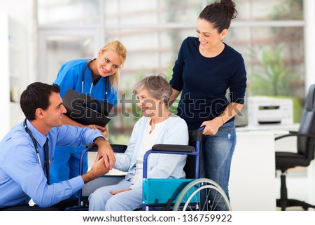 friendly male doctor comforting senior patient - stock photo