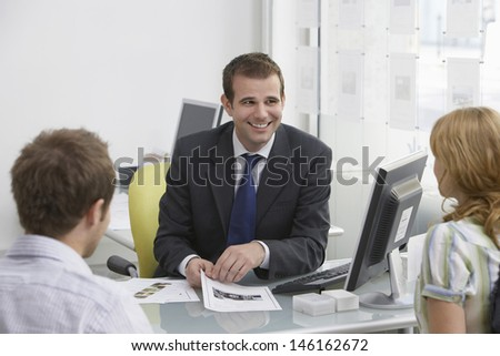 Friendly male real estate agent with a couple in the office - stock photo