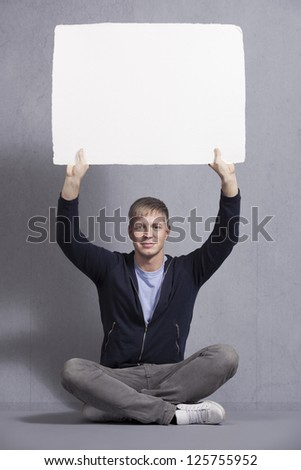 Friendly man holding up white empty signboard with space for text isolated on grey background. - stock photo