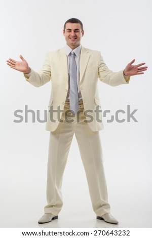 Friendly man in a white suit in studio. Makes hand gestures. - stock photo