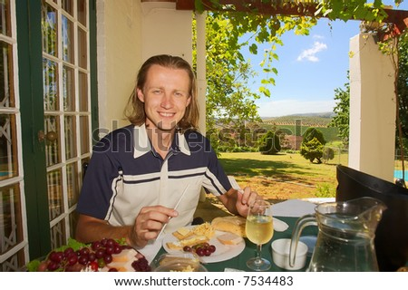 Friendly man smiles while dining in outdoor winefarm restaurant among awesome mountains (focus on face). Shot near Stellenbosch, Western Cape, South Africa.