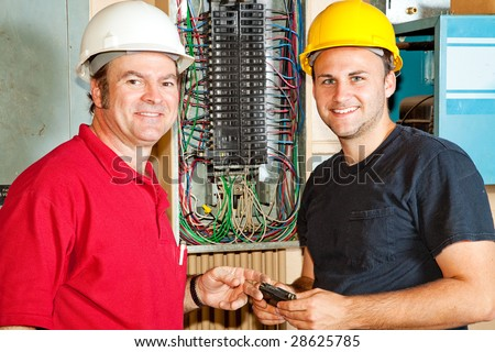 Friendly master electrician and apprentice working on breaker panel. - stock photo