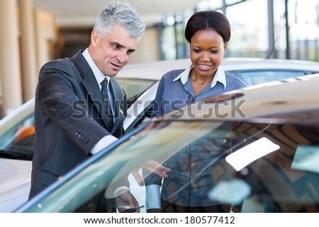 friendly mature car dealer showing new car to african customer - stock photo