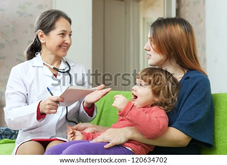 friendly mature children's doctor examining baby in home - stock photo