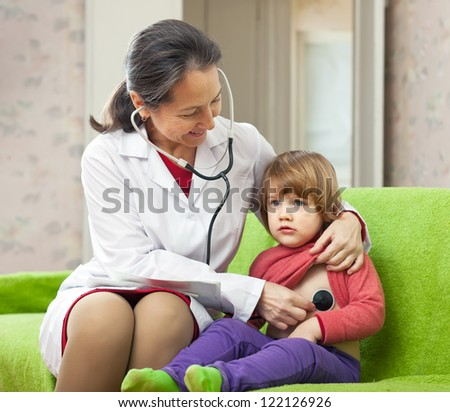 friendly mature children's doctor examining 2 years child with  stethoscope at home - stock photo