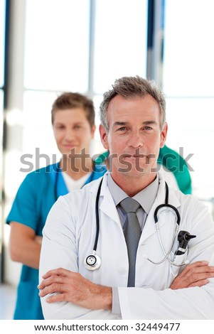 Friendly mature doctor leading his team in hospital - stock photo