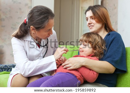 friendly mature pediatrician doctor examining baby - stock photo