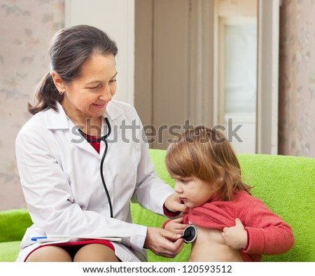 friendly mature pediatrician doctor examining baby with  phonendoscope