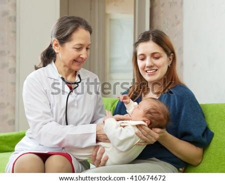 friendly mature pediatrician doctor examining newborn   - stock photo