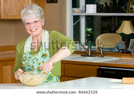 Friendly mature woman with a nice smile and white hair baking cookies in the kitchen. - stock photo