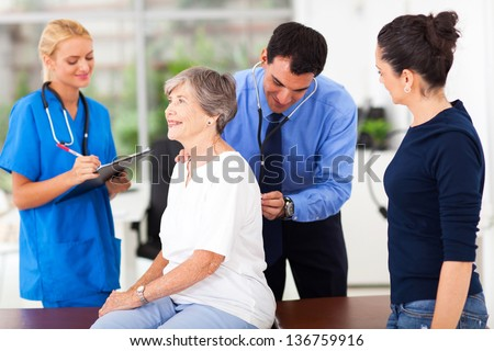friendly medical doctor examining senior patient in office - stock photo