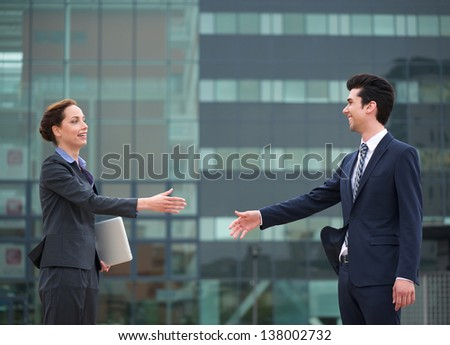 Friendly meeting with a handshake between a business woman and a businessman - stock photo