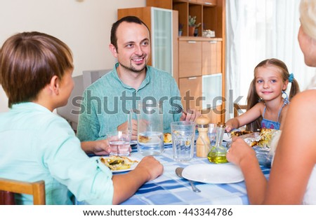 Friendly mother, father and kids sitting at the table at the home and eating