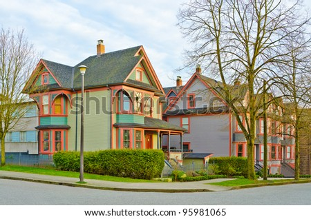 Friendly neighborhood. Colourful houses over overcast sky and trees in front in Vancouver, Canada.