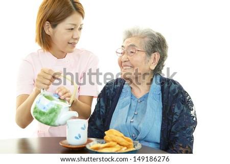 Friendly nurse cares for an elderly woman - stock photo