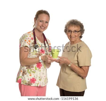Friendly Nurse Helping Elderly Senior with Coffee Isolated on White Background - stock photo