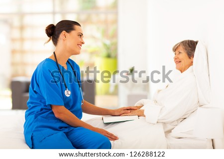 friendly nurse visiting recovering senior patient - stock photo
