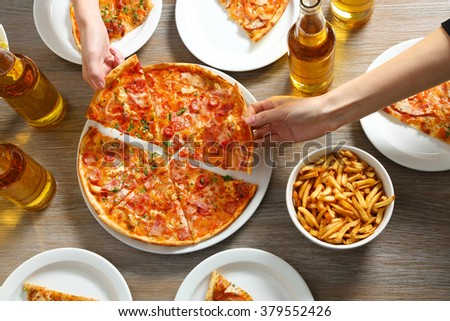 Friendly party with hot pizza and drinks, close up - stock photo