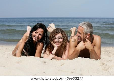Friendly people lying on sandy beach - stock photo