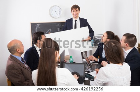 Friendly people presenting new products plan at poster during conference  indoors - stock photo