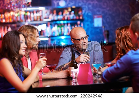 Friendly people with drinks gathered in the bar
