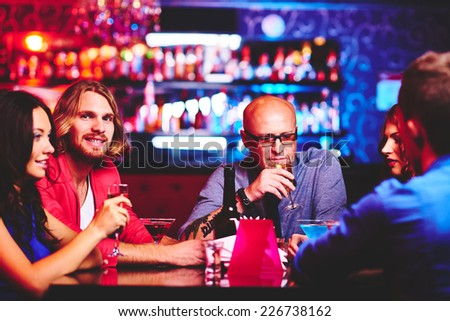 Friendly people with drinks spending time in the bar - stock photo