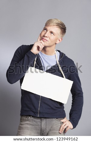 Friendly pondering man presenting white empty signboard with space for text isolated on grey background. - stock photo