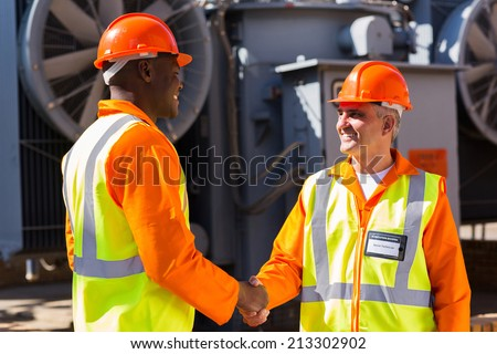 friendly power company co-workers hand shaking in electrical substation - stock photo