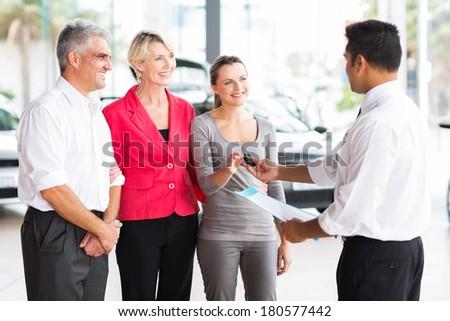 friendly salesman handing car key to customer in showroom - stock photo