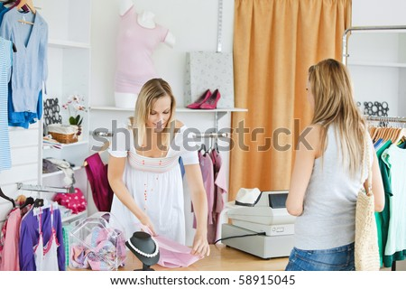 Friendly saleswoman packing clothes in a bag  in a clothes store