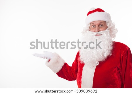 Friendly Santa Claus is raising his hand sideways and presenting something. He is looking forward and smiling. Isolated on background and copy space in left side - stock photo