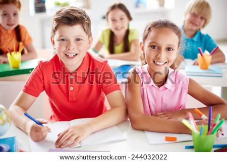 Friendly schoolkids looking at camera at lesson - stock photo