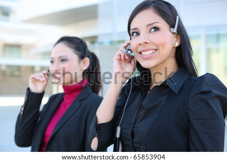 Friendly secretary Women on telephone headset in an office environment - stock photo