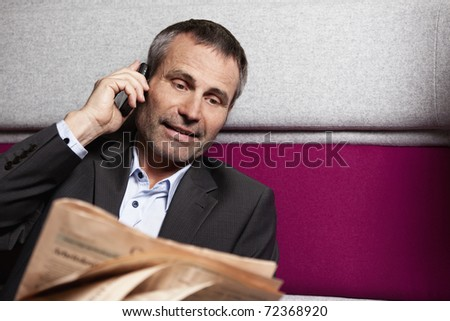 Friendly senior business executive in grey suit talking on cell phone and reading newspaper. - stock photo