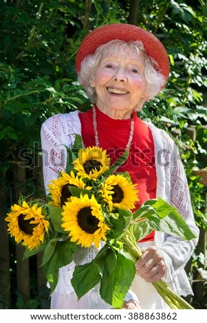 Friendly senior lady in a stylish red outfit with a bunch of bright yellow fresh sunflowers in her hand standing outdoors in a lush green summer garden smiling at the camera. - stock photo