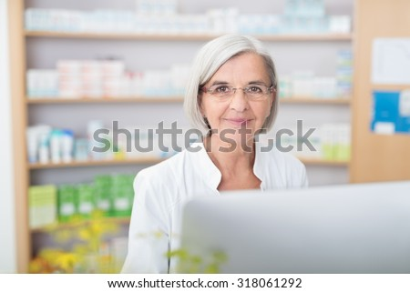 Friendly senior pharmacist waiting to help standing behind her computer in the pharmacy with an attentive look and warm smile - stock photo